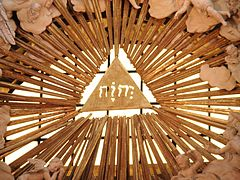 A triangle with the four letters of the tetragrammaton--YHWH--in the center of a triangle, which itself is surrounded by clouds. It is part of a 3-d stained glass structure.