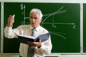 white-haired speckled man with book open, teaching math, equation on board behind