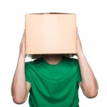 man in green shirt with box over his head