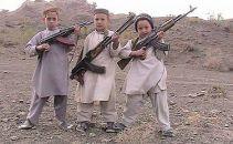 three pre-teens holding Kalashnikov's rifles