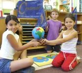three Montessori students with globe