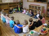 kids sitting in square-shaped 'circle,' their arms on each others' shoulders