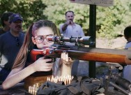 girl looking through rifle scope at firing range