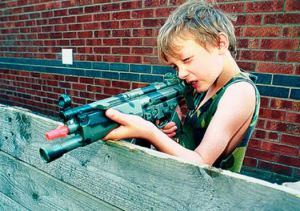 Boy firing toy rifle