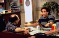 Jerry Seinfeld sitting across a table from George Costanza
