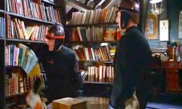 Montag's captain with his arm sweeping books off of a shelf